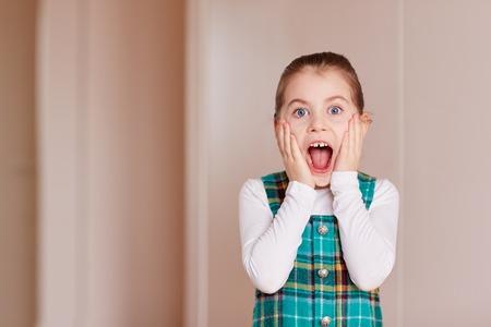 ojos azules: Una niña linda abriendo la boca a la cámara dentro de la sala blanca