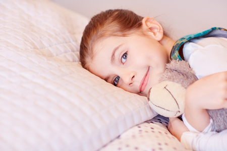 adoring: A cute little girl lying on her bed with her teddy Stock Photo