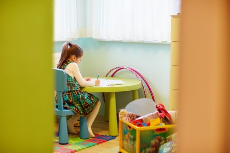 quietly: A little girl drawing quietly in her room