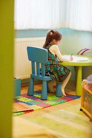 little girl dress: A little girl drawing quietly in her room