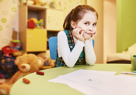 smirk: A little girl with a naughty smirk on her face in her playroom Stock Photo