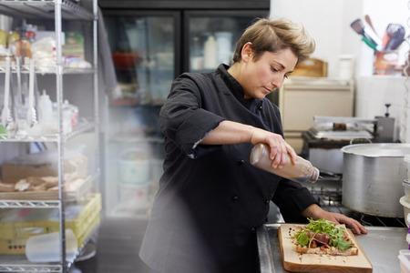 balsamic: A female chef drizzling balsamic vinegar on an open sandwich