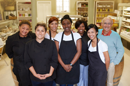 deli: A group of deli workers standing in their shop Stock Photo