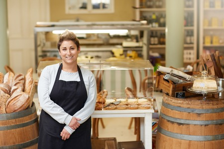 female business: A young deli employee standing in front of the pastry display
