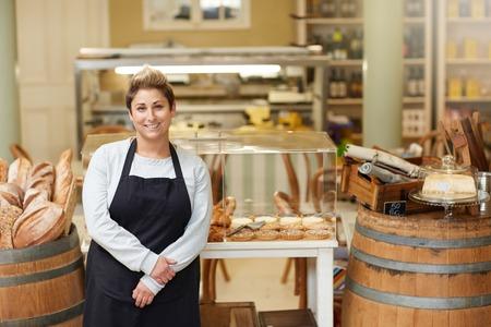Un joven empleado delicatessen de pie delante de la pantalla de pastelería
