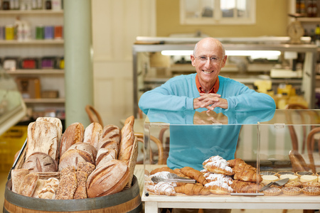 deli: An elderly deli owner standing at the pastry display in his shop Stock Photo