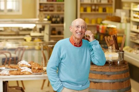 An elderly deli owner talking on the phone in his shop Imagens