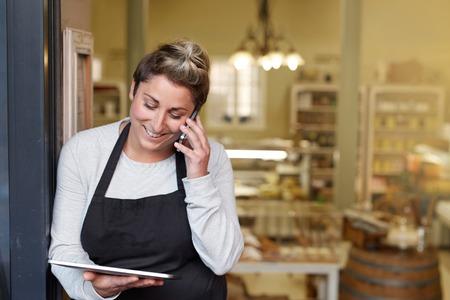 Een jonge delicatessenwinkelwerknemer die op de telefoon spreekt terwijl het werken aan een tablet