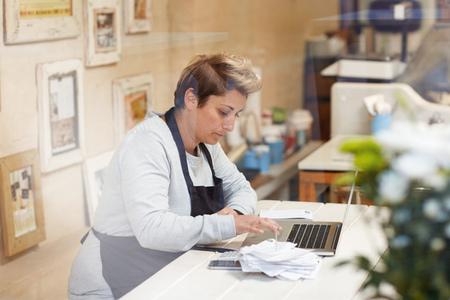 impuestos: El dueño de una tienda de delicatessen femenina haciéndola impuestos en su tienda