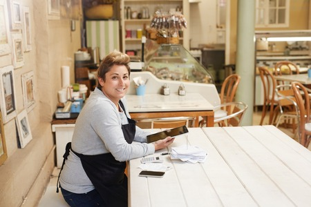 A female deli owner doing her taxes in her shop