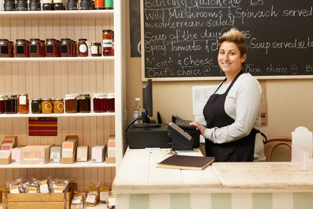 A young deli worker standing behind the counter Standard-Bild
