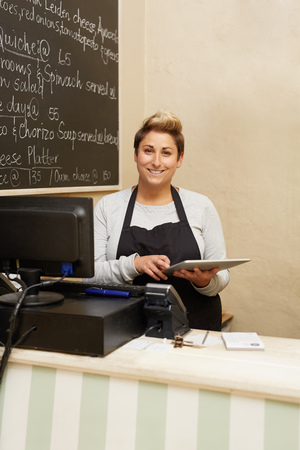 worker working: A young deli worker standing behind the counter while working on her tablet Stock Photo