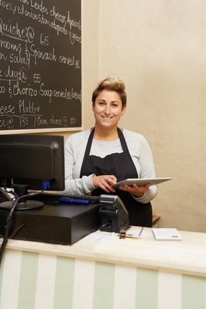 obrero trabajando: Un joven trabajador delicatessen de pie detrás del mostrador mientras trabajaba en su tableta