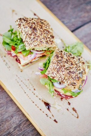 high angle shot: High angle shot of a fresh sandwich made with seeded bread, with salami, tomato, chees and lettuce, presented on a rustic wooden board Stock Photo