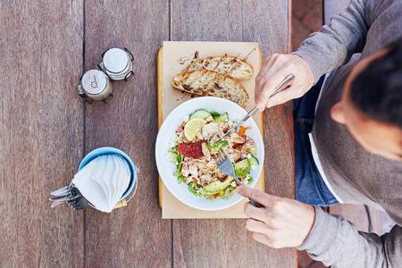 Overhead-Schuss von einem Mann an einem Holztisch auf seiner Mittagspause sitzen einen frischen Salat mit Huhn essen, Avocado, Getrocknete Tomaten mit Gewürzen und serviettes einsatzbereit