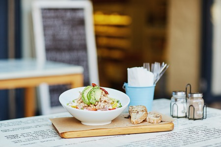 eatery: Fresh chcken and avacado sald in a presented in a bowl on a wooden board, alongside some freshly sliced bread laid out on a table outside a gourmet delicatessen eatery