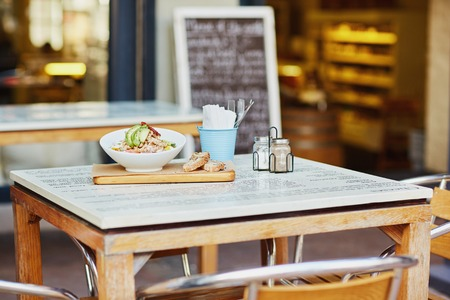 lunch table: Table outside a gourmet dlicatessen with a healthy salad presented on a wooden board with fresh bread and ready for a customer to eat