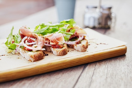 parma ham: Gourmet meal of bruschetta topped with toamto, onion, parma ham and rocket, presented on a wooden board with condiments in the background