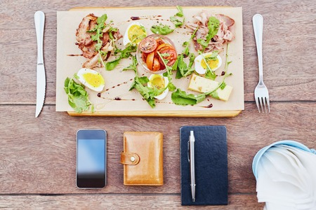 well laid: Overhead view of a fresh salad platter of meat, chees, egg and tomato with a business persons phone, diary and wallet laid on the table as well Stock Photo