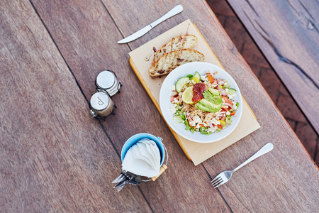 serviettes: Overhead shot of a wooden table simply set with a fresh salad accompanied by slices of bread, cutlery, serviettes and cutlery