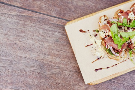 parma ham: Cropped overhead view of a delicious gourmet bruschetta with fresh parma ham, crsip rocket leaves and petso, presented on a rustic wooden table Stock Photo