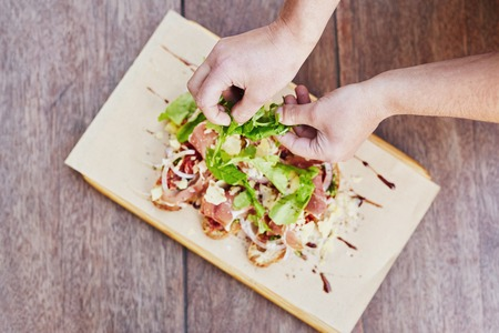 artisanal: Overhead shot of a chefs hands preparing a delicious bruschetts by adding rockets leaves to the presentation Stock Photo