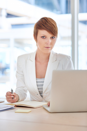 office wear: Modern young businesswoman with a short hair style and and neat office wear, sitting at her desk with paperwork and her laptop, looking seriously at the camera