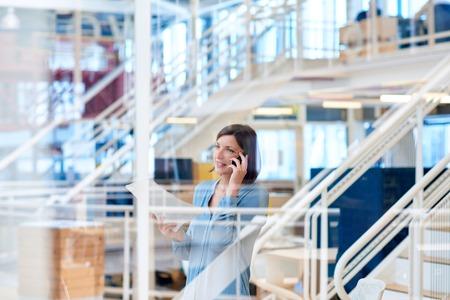 Aantrekkelijke eigentijdse onderneemster die op haar telefoon spreken terwijl wat administratie houden en weg kijken, zoals die door het glas van een binnenlands venster in een moderne bureauruimte wordt gezien