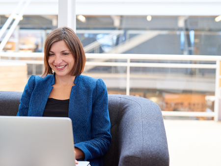 broadly: Businesswoman in a stylish jacket, sitting on an office couch smiling broadly while working on her laptop computer