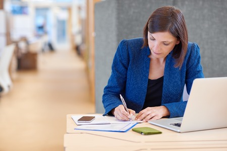 busineswoman: Stylish young busineswoman writing while working on paperwork at her desk in a bright shared office with a cucbicle divider behind her