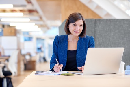 cubicle: Portrait of an attractive businesswoman working at her desk in a shared office space, looking at the camera with a gentle and confident smile