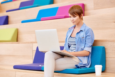 public space: Pretty female university student sitting on colourful cushions in a public space working on her laptop with a takeaway coffe next to her Stock Photo