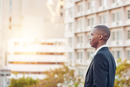 african descent: Young businessman of African descent standing in a city, looking away into the distance so that his face is in profile Stock Photo