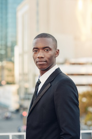 achiever: Portrait of a young African man wearing a smart suit and looking like he could be a finance entrepreneur, standing in a city and looking at the camera with a serious yet optimistic expression Stock Photo