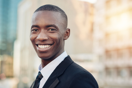 broadly: Portrait of a handsome young African businessman standing outdoors in a city, wearing a smart suit and tie and smiling broadly while looking confidently at the camera Stock Photo