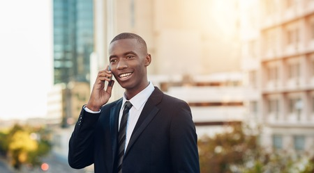 african descent: Confident young businessman of African descent wearing a smart suit, standing in a modern city and talking on his mobile phone and smiling Stock Photo