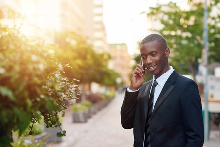 african descent: Handsome young man of African descent wearing a smart suit and tie, smiling while talking on his mobile phone, standing on a city sidewalk with trees and sunflare