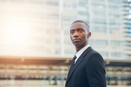 african descent: Handsome young businessman of African descent wearing a smart suit, looking up and away with a serious expression, with city buildings and sunflare in the background
