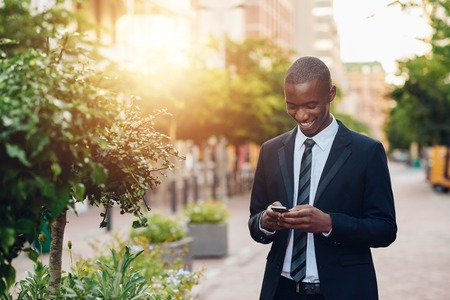 Young professional African businessman wearing a smart suit and tie, smiling while reading a message on his mobile phone, standing in a city walkway with green plants and gentle sunflare