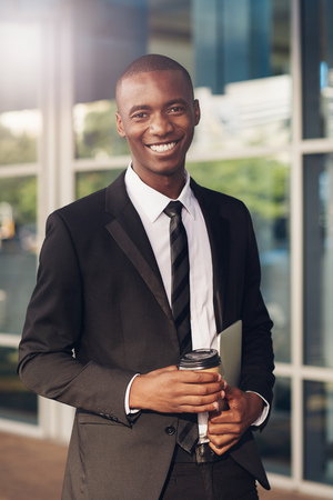 african descent: Young businessman of African descent smiling at the camera while holding a takeaway coffee and digital tablet, on a city sidewalk