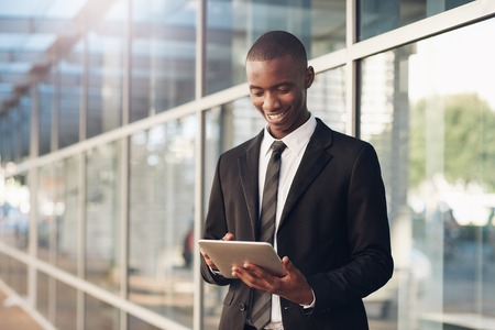 african descent: Young man of African descent in a business suit, smiling while using a digital tablet, standing on a city sidewalk with large windows behind him Stock Photo