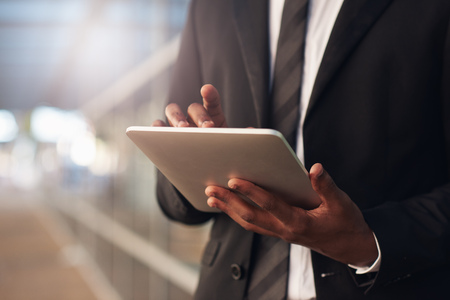 achiever: Cropped image of the hands of an African businessman wearing a smart suit, using a modern digital tablet with office windows behind