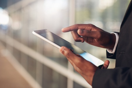 achiever: Cropped closeup of the hands of a businessman of African descent holding and using a digital tablet, wiht blurred office windows in the background Stock Photo