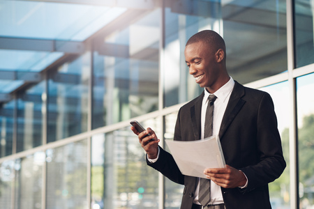 Smiling young man of African descent wearing a smart business suit and looking at the screen of his mobile phone, while standing on the sidewalk of a city and holding some paperwork Stock Photo