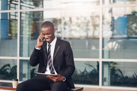 phone business: Young African businessman sitting outside his office on a bench laughing while talking on his mobile phone and looking at his digital tablet Stock Photo