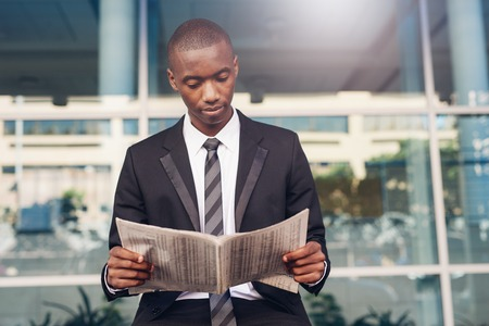 achiever: Handsome young businessman of African descent sitting outdoors in a city reading a newpaper that has information about finance, with large modern office space behind him