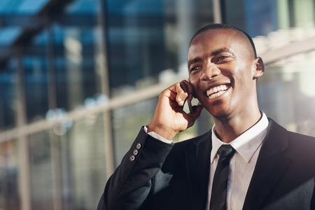 Confident young businessman of African descent, laughing and smiling while talking on his mobile phone with a modern office building in the background Stock Photo