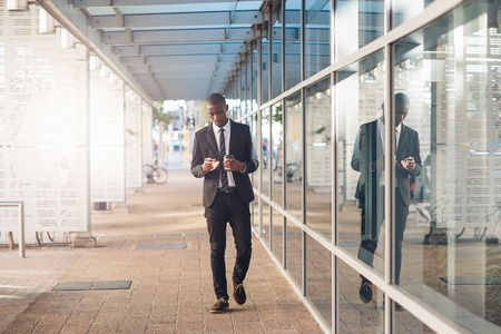 achiever: Full length shot of a young African businessman wearing a contemporary suit, walking past office windows on a city street, carrying coffee and looking at his mobile phone while reading a message