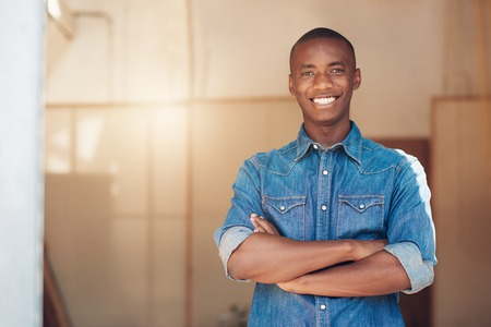 カメラに自信を持って笑顔新しいスタジオ スペース、組んで、腕をアフリカ降下立ってのハンサムな若い男の肖像