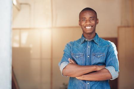 그의 팔을 서 아프리카 출신의 잘 생긴 젊은 남자의 초상화는 새로운 스튜디오 공간에서 자신감 카메라에 미소를 넘어